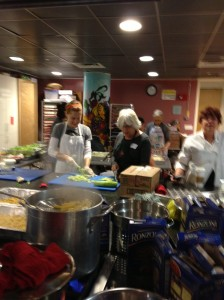 Pasta boiling on the stovetop of the JCC kitchen with salad makers in the back